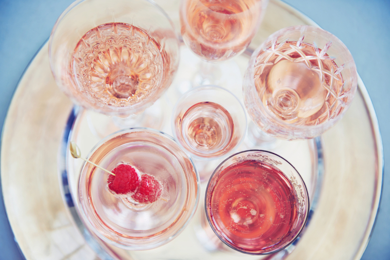 Overhead of vintage glasses with pink rosé champagne on a silver tray