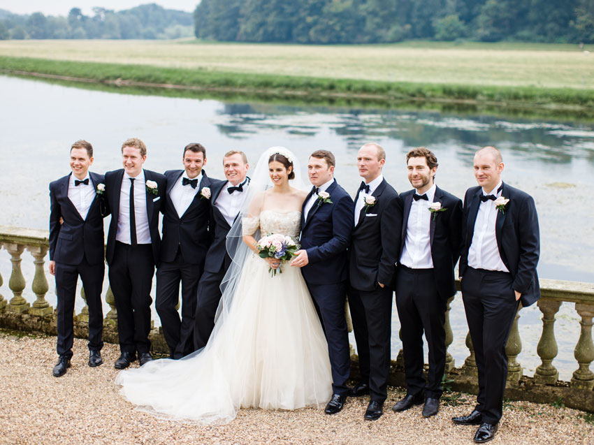 bride-with-groomsmen-overlooking-lake-stately-home-Stoneleigh-Abbey---patchwork