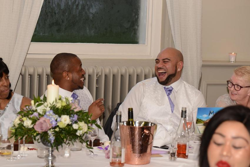Black Gay Wedding Couple laughing during reception