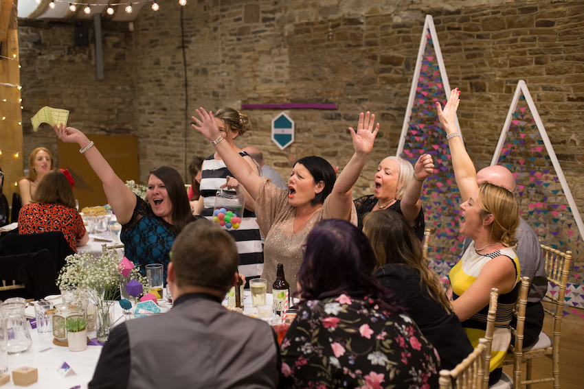 Group of wedding guests taking part in quiz and cheering, sitting at table