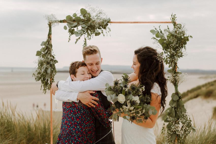 Groom hugging guest at beach wedding