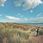 couple in wedding attire in sand dunes on beach