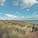 couple in wedding attire in sand dunes on beach