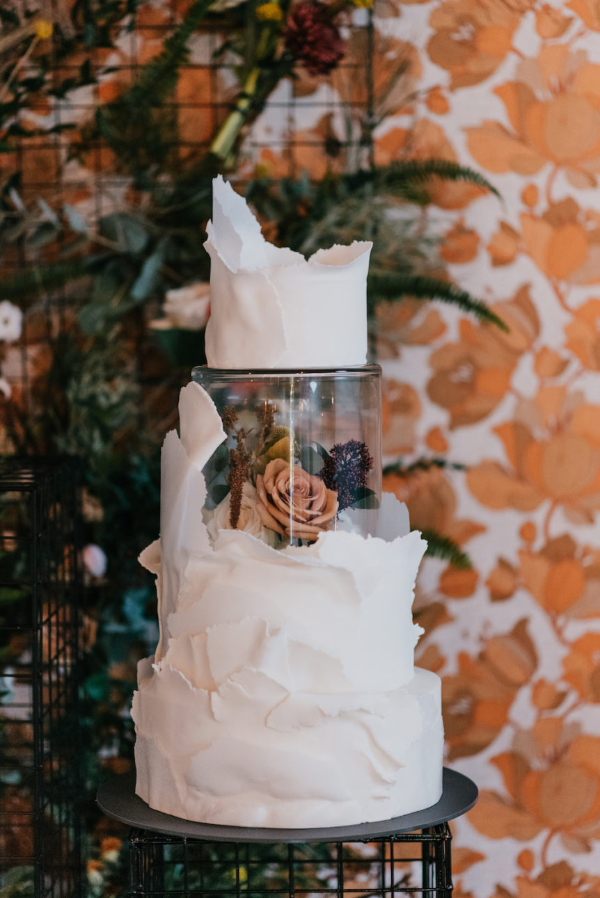 Four tier modern style wedding cake, with white icing and middle glass section, photo taken by Laura Martha Photography