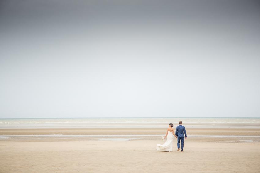 couple in wedding attire on deserted beach