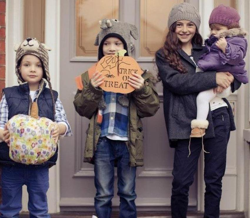 Four kids outside a front door dressed in winter clothes and hats holding Halloween props