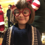 Girl with brown hair wearing Christmas glasses, scarf and red bow