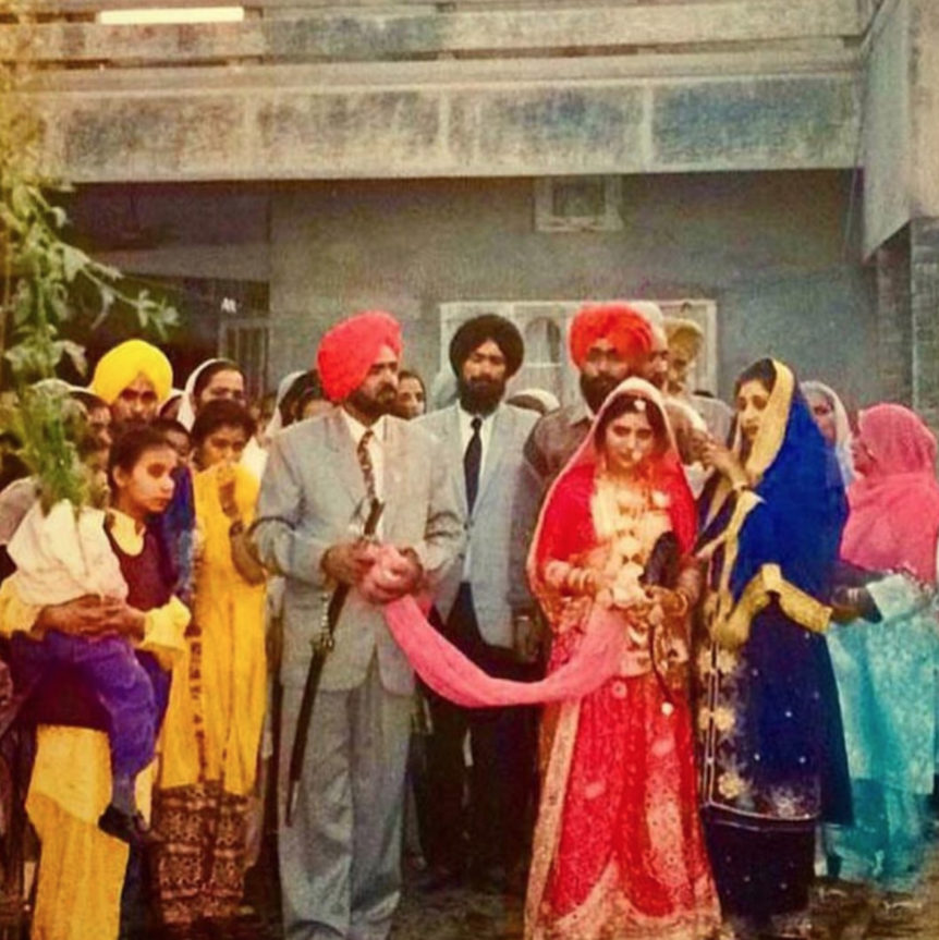 An Indian bride in a red wedding dress and her husband standing beside her, with the wedding party behind