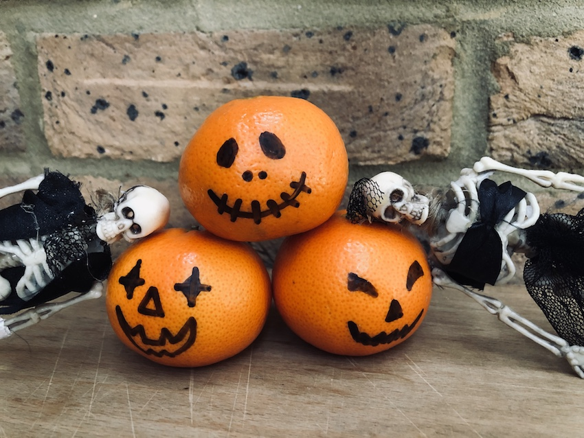 Halloween clementines decorated to look like mini pumpkins