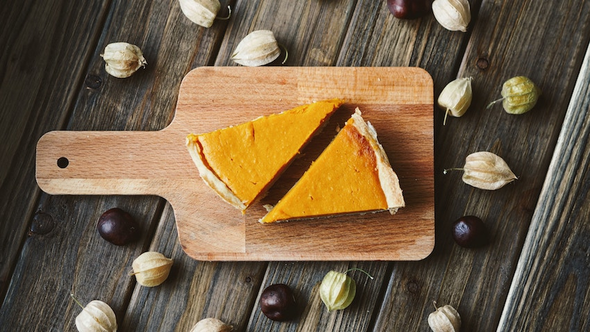 Two slices of pumpkin pie on a wooden chopping board