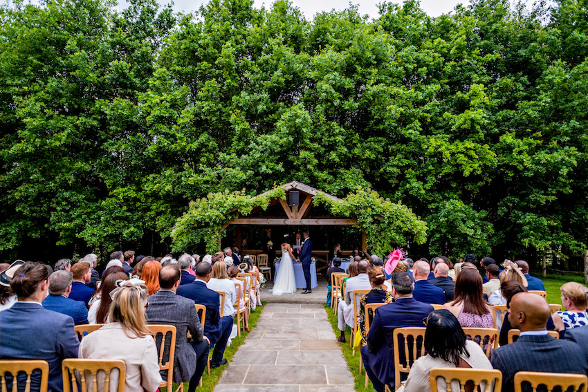 Couple getting married outdoors against backdrop of trees with guests looking on