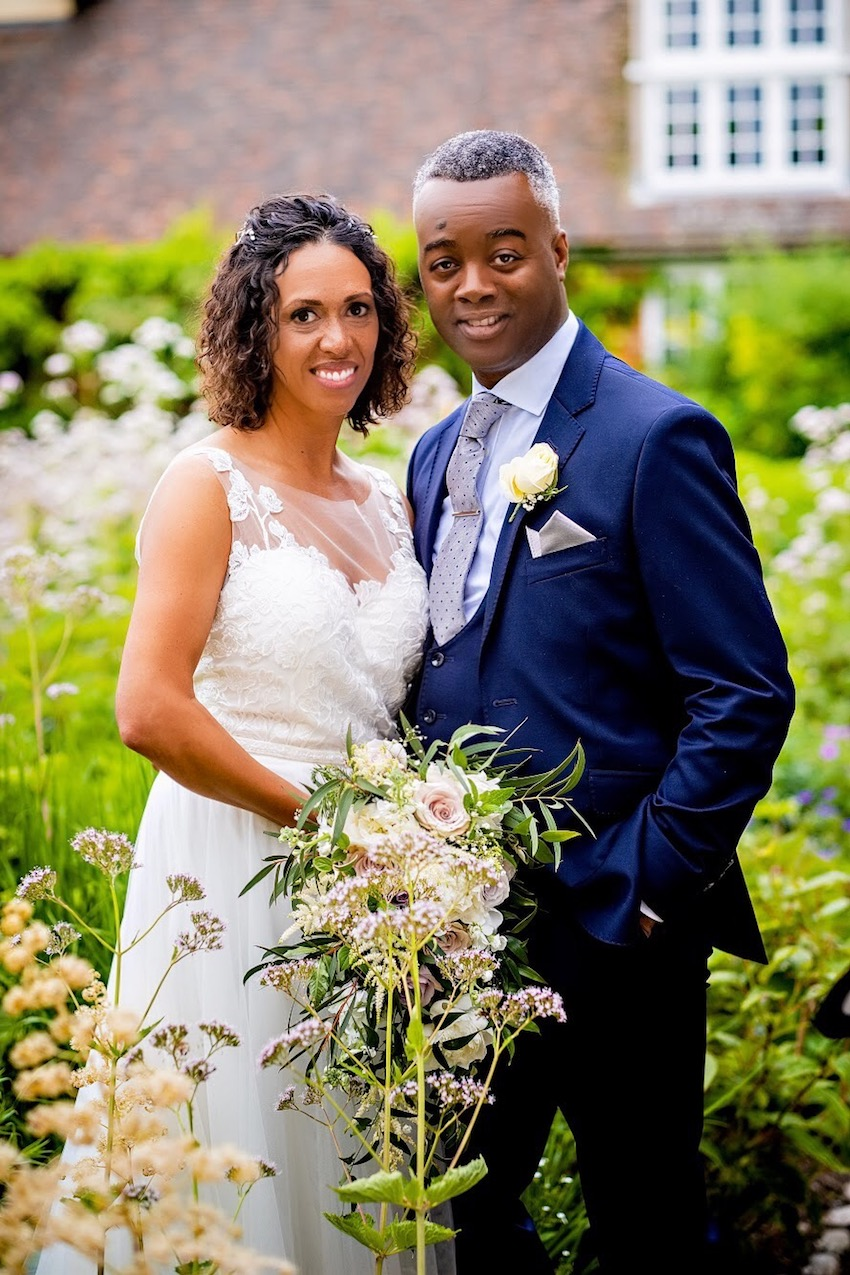 Black woman holding bouquet and black man in dark suit posing for wedding day photo