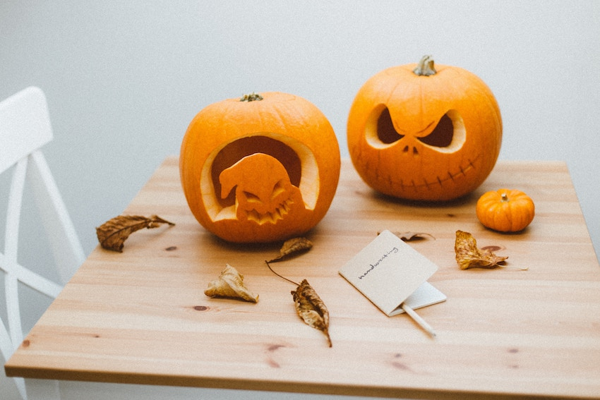 Two carved Halloween pumpkins on a wooden table