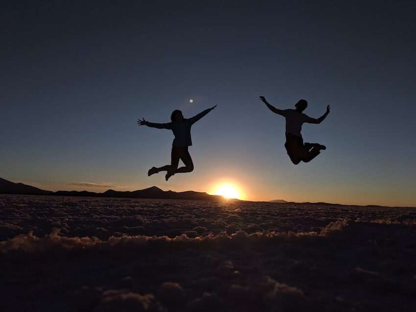 Couple on honeymoon jumping in the air with sunset behind