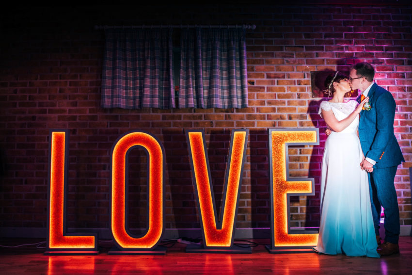 Bride and Groom standing by big LOVE sign