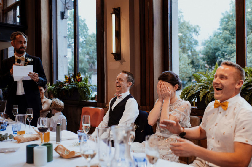 Bride and Groom laughing at speeches on wedding day
