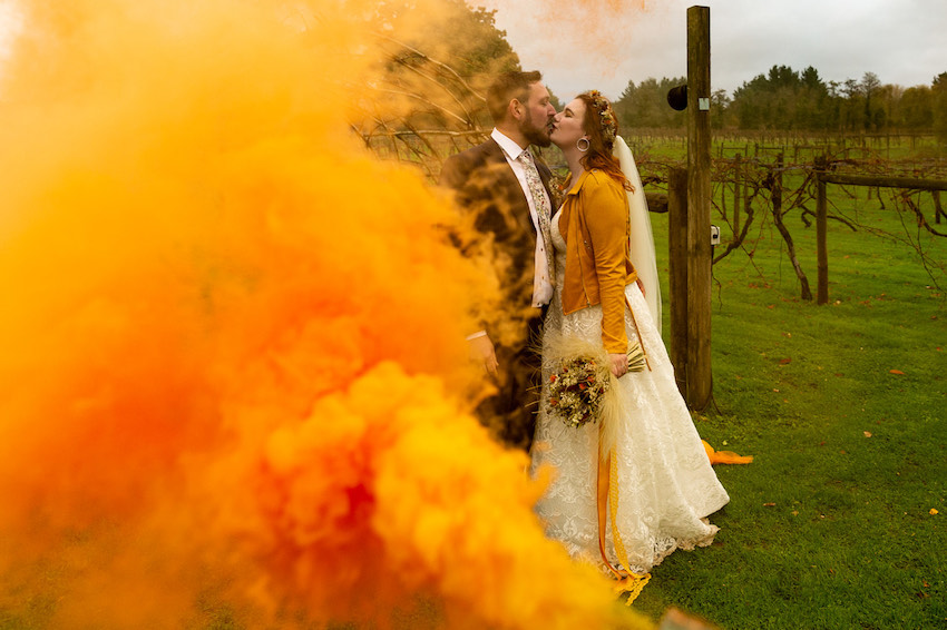Couple kissing in orchard on wedding day in cloud of yellow smoke