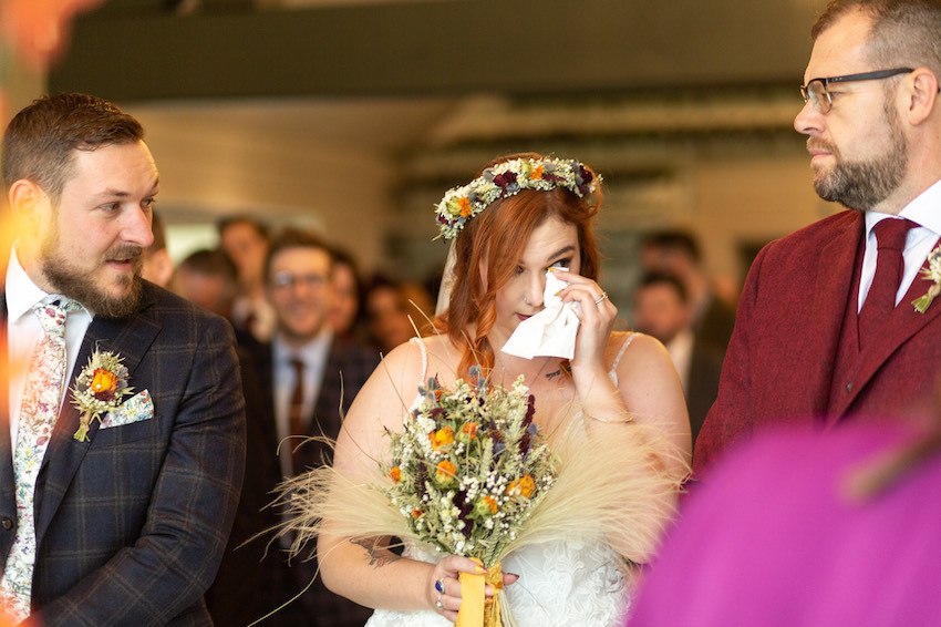 Bride wiping tear away during wedding ceremony