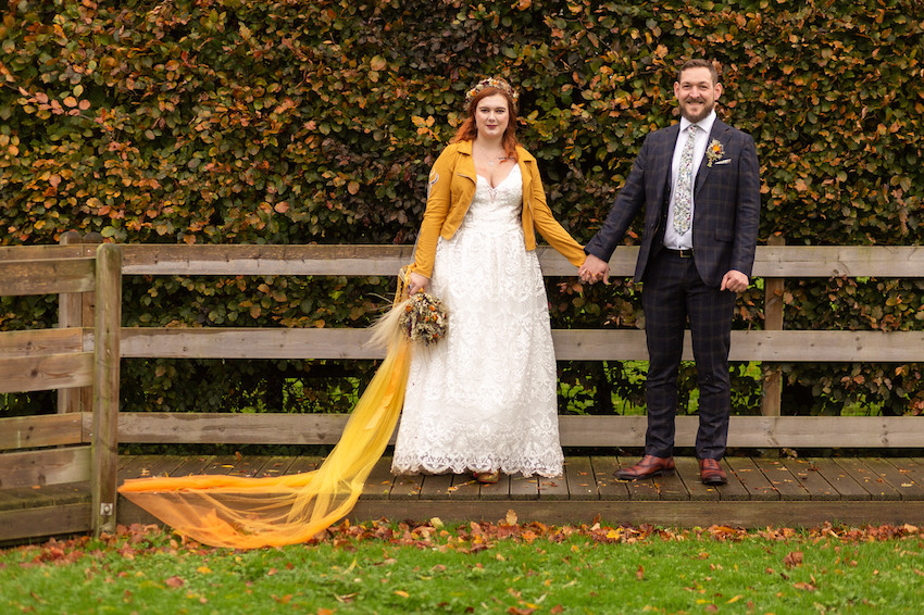 Bride and Groom standing outside. Bride in yellow leather jacket and yellow veil
