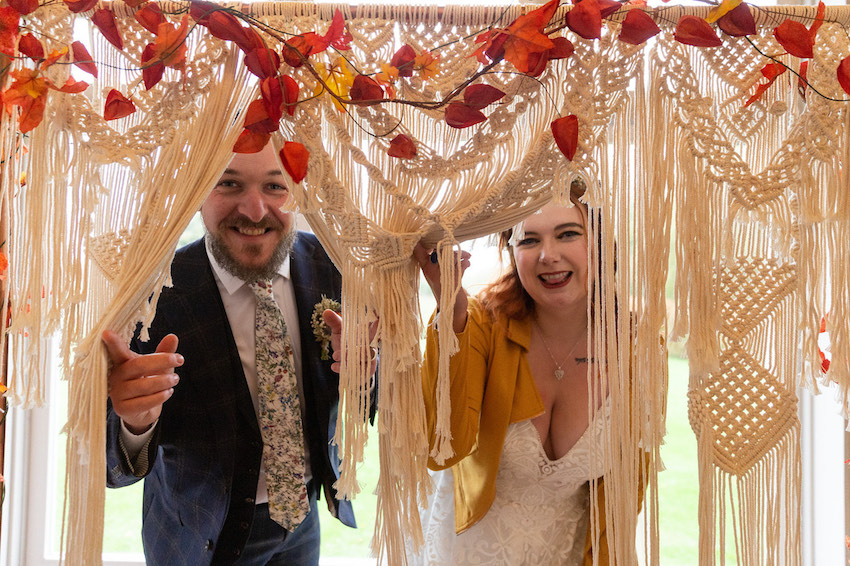 Bride and Groom peeping through crochet decorative curtain