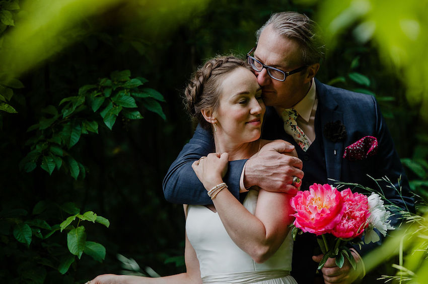 Groom with arm around Bride, in gardens