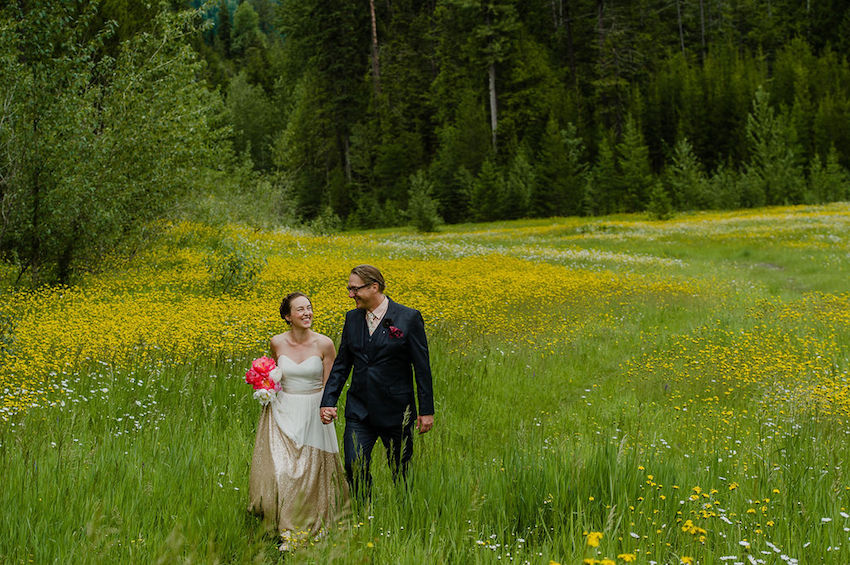 Bride and Groom walking through field of long grass