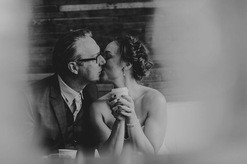 B+W image of Bride and Groom kissing while holding coffee