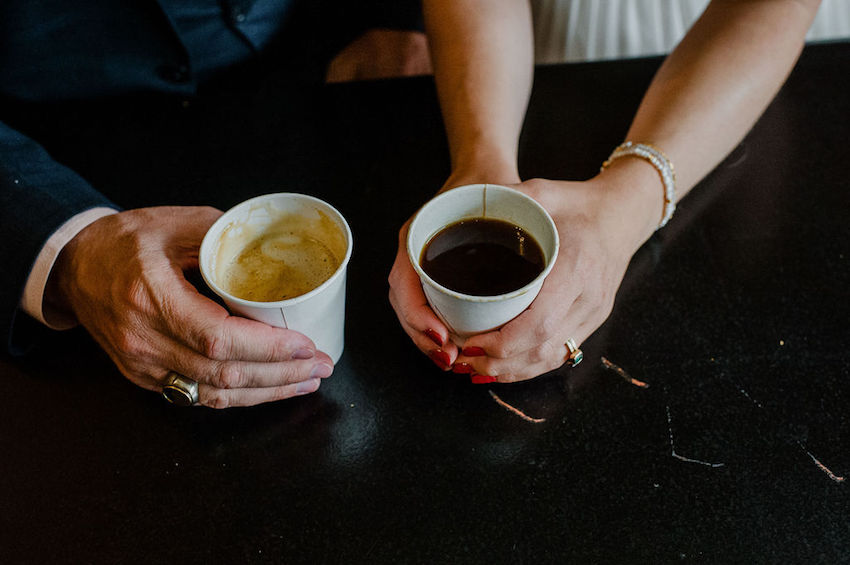Close up of Bride and Groom's hands holding cups of coffee