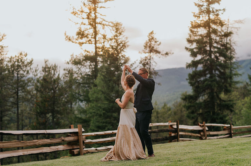 Bride and Groom dancing outside overlooking forest