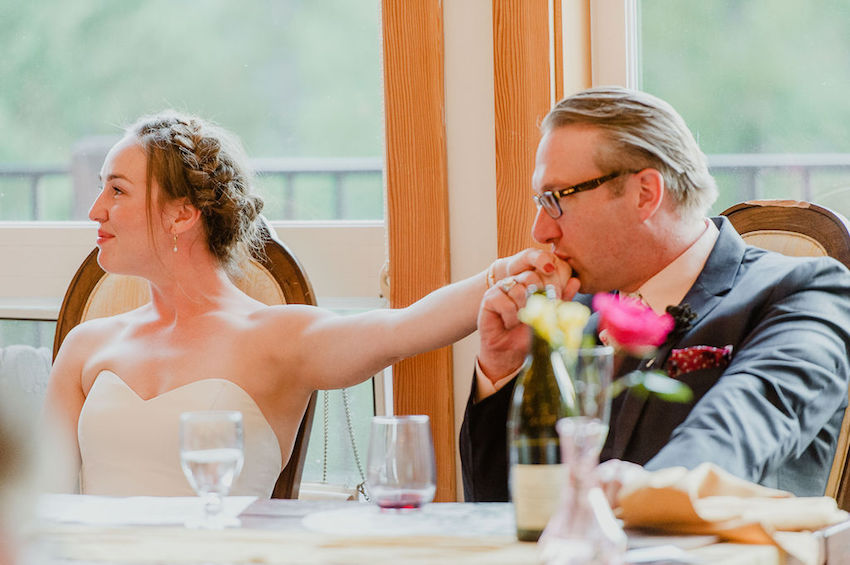 Groom kissing bride's hand during wedding reception
