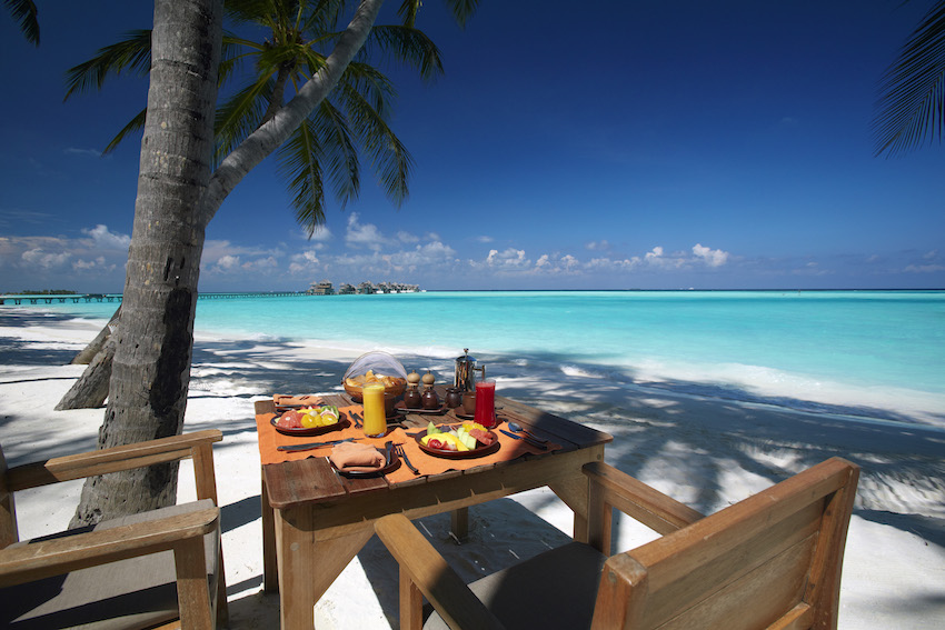 Table set for breakfast on beach, overlooking turquoise ocean, The Maldives