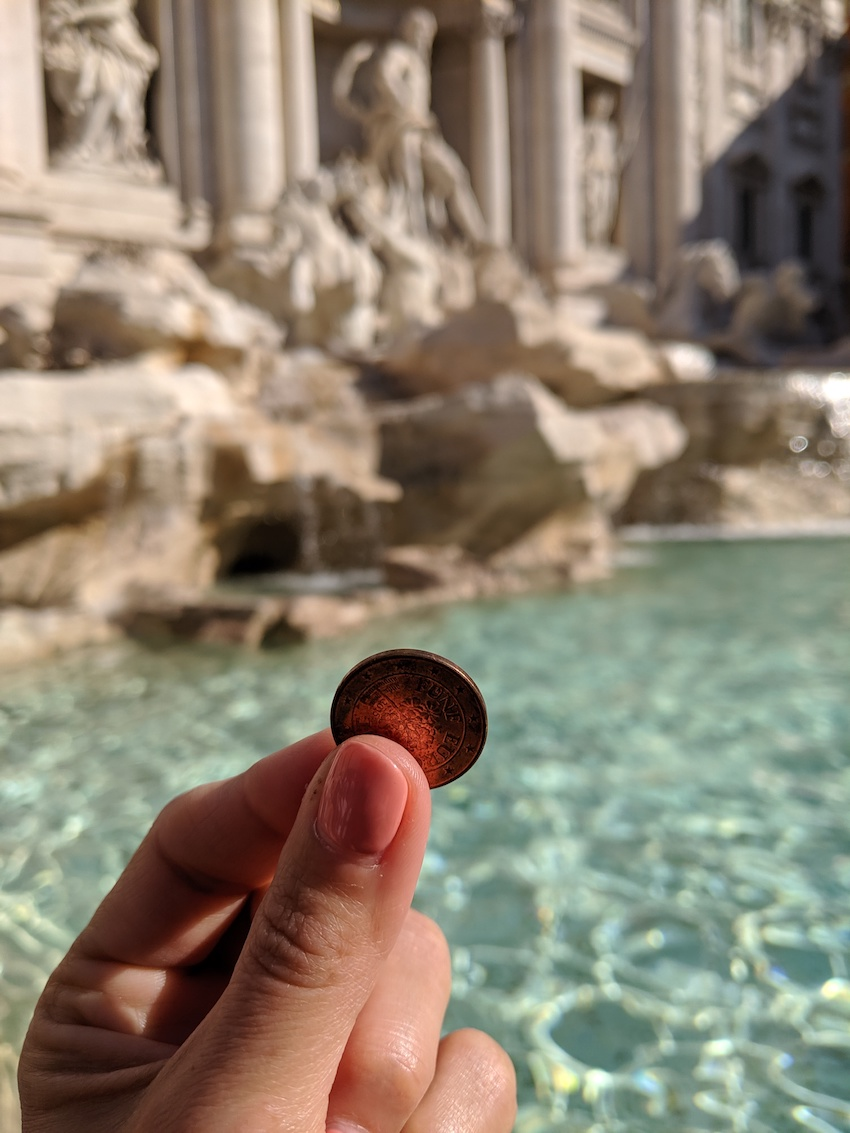 Hand holding up a Euro cent coin in front of water