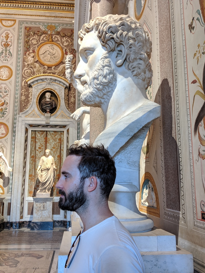 Man standing next to statue in Italy