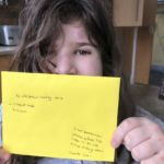 Girl holding up hand written letter