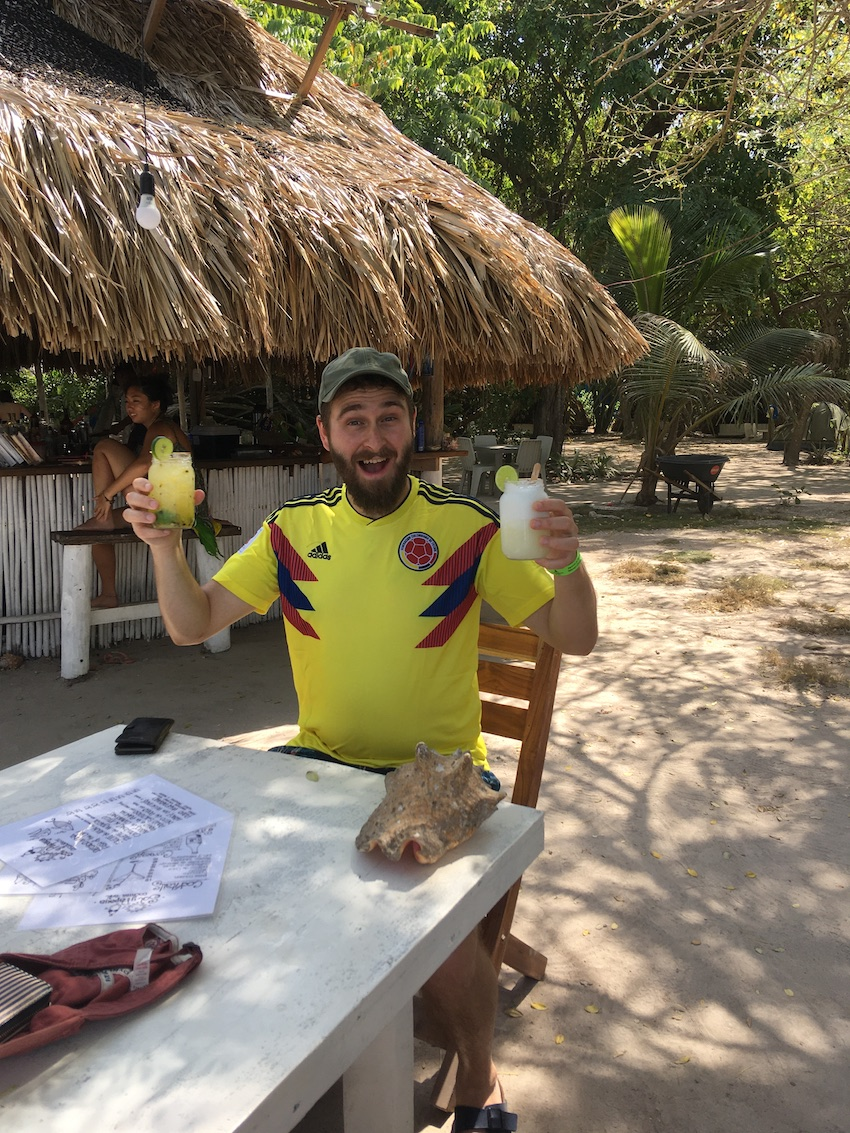 Man on honeymoon in Colombia having cocktails on beach