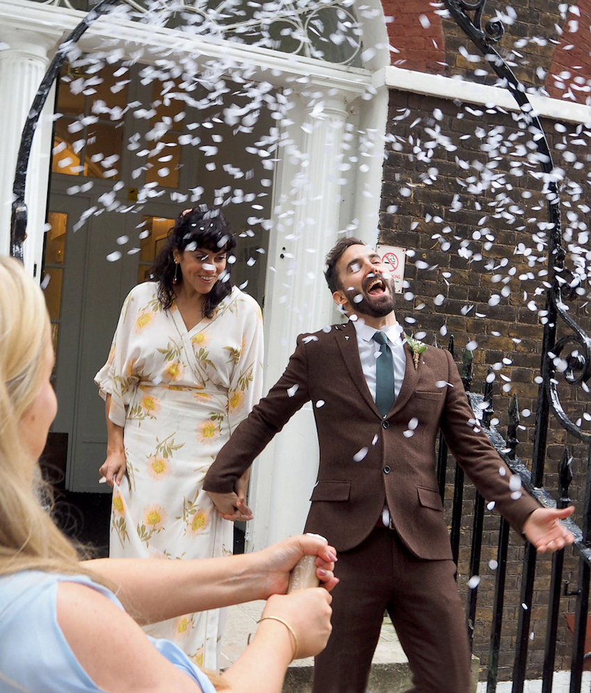 Couple on wedding day walking out of ceremony in shower of confetti