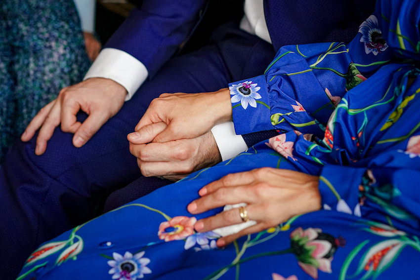 Couple on wedding day holding hands. Bride and Groom wearing blue