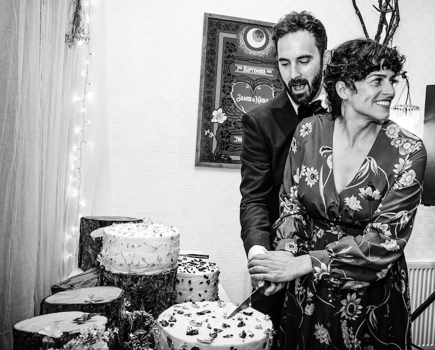 black and white image of couple on wedding day cutting cake