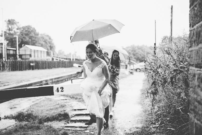 Bride followed by groom and bridesmaid, stepping through puddles having umbrella held for her