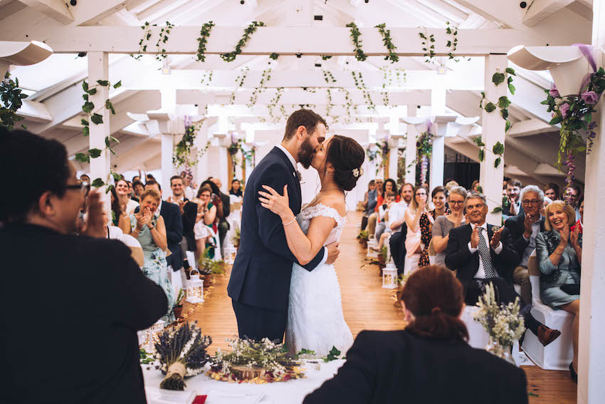 Bride and Groom kiss in front of guests during wedding ceremony