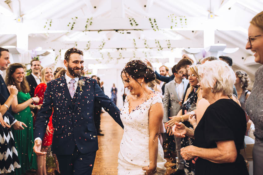 Bride and Groom laughing and being showered in confetti by guests