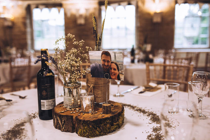 Wedding breakfast tables set with natural decor, logs and tea lights