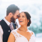 Close up portrait of bride and groom smiling at each other in doorway in sunshine
