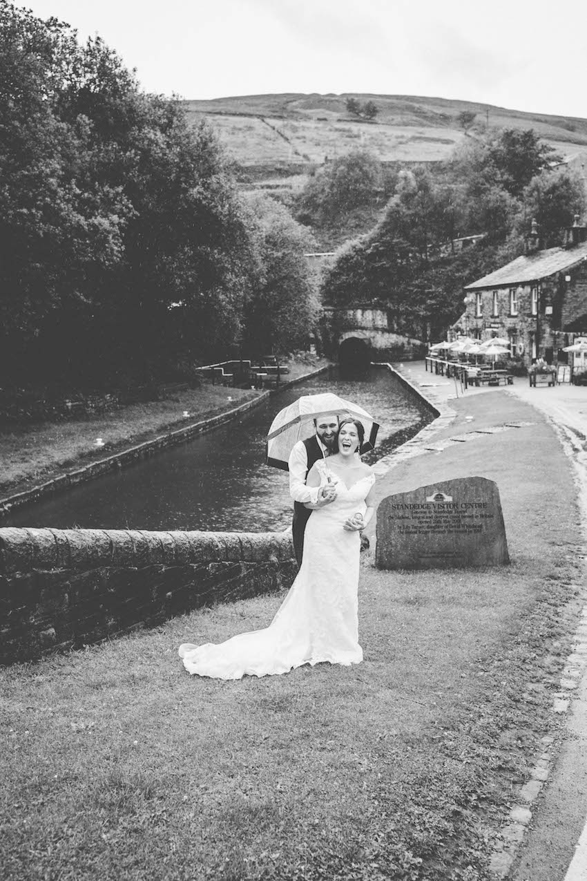 Bride and Groom standing by river under umbrella laughing