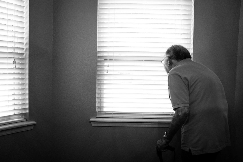 Elderly man standing at window with blind down