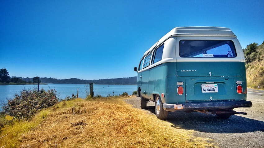 Blue Campervan parked beside water
