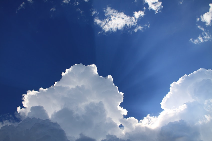Sun shining from behind clouds in blue sky