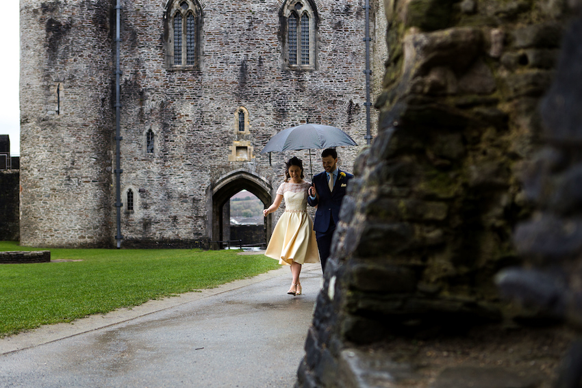 Bride and groom walking in grounds of Caerphilly Castle under umbrella