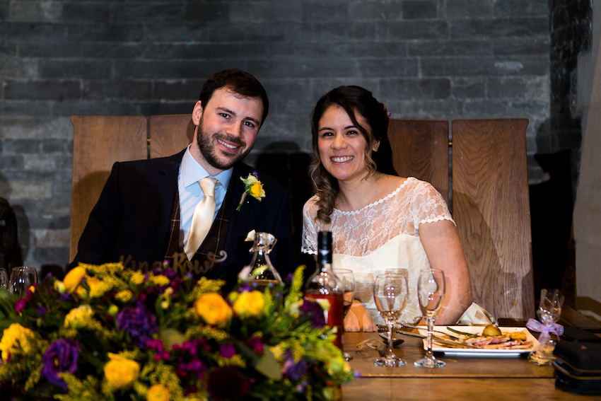 Bride and groom at wedding reception with flowers on table