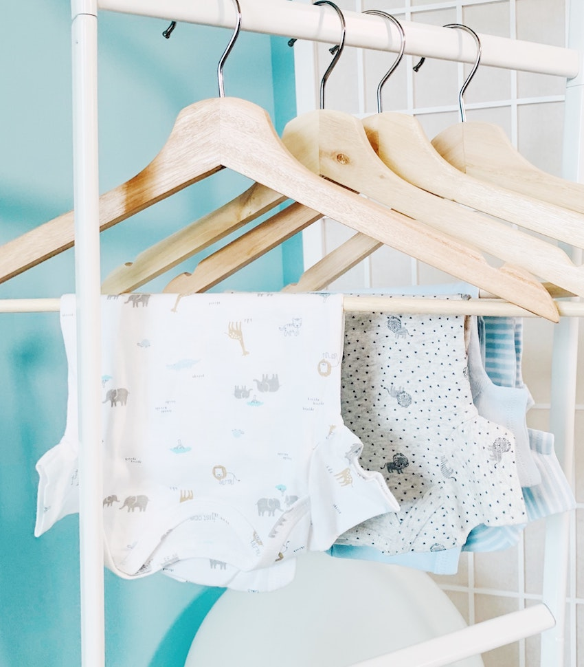 Baby vests hanging on hangers on rail